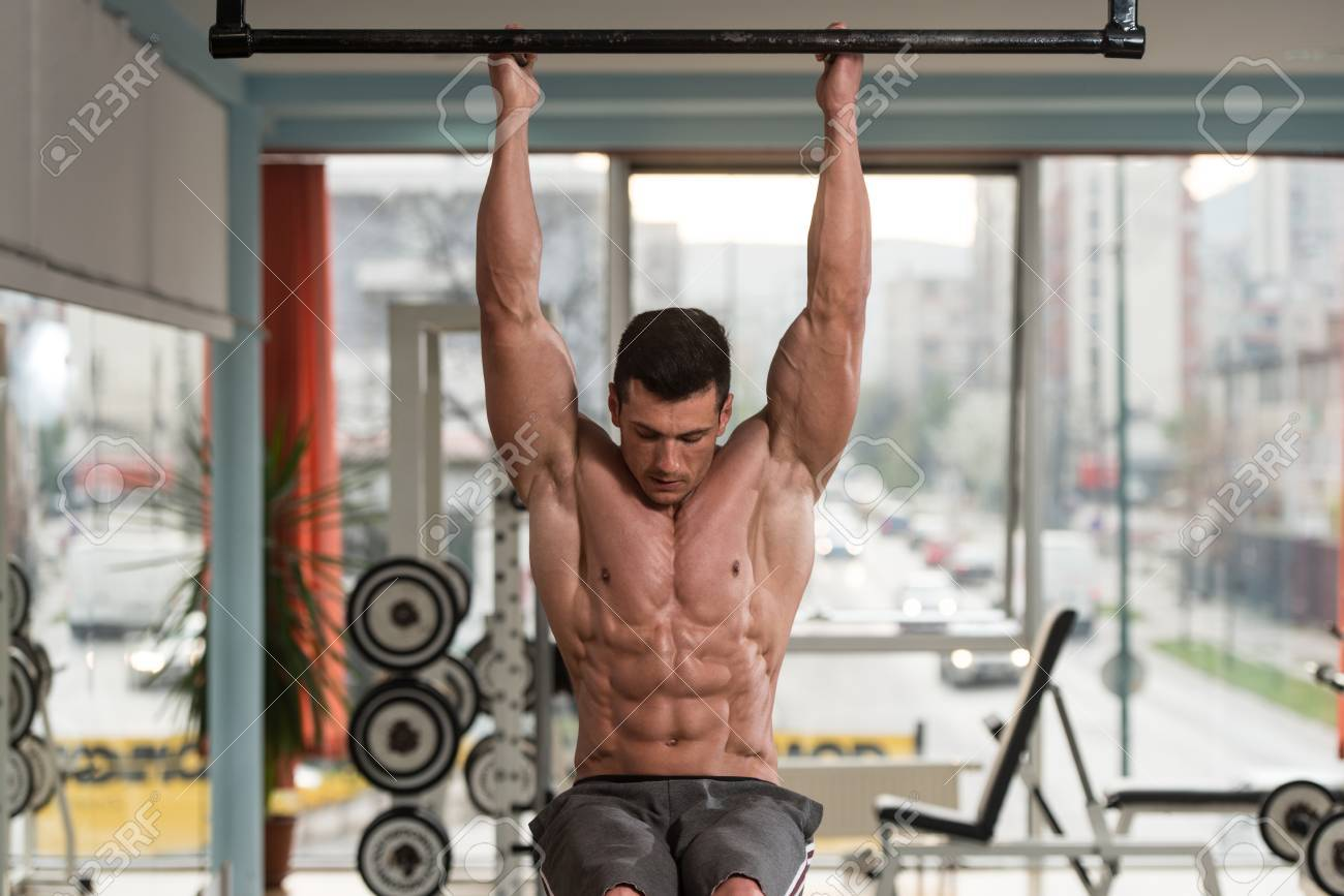 Young Man Performing Hanging Leg Raises Exercise - One Of The Most Effective Ab Exercises Stock Photo - 44727385