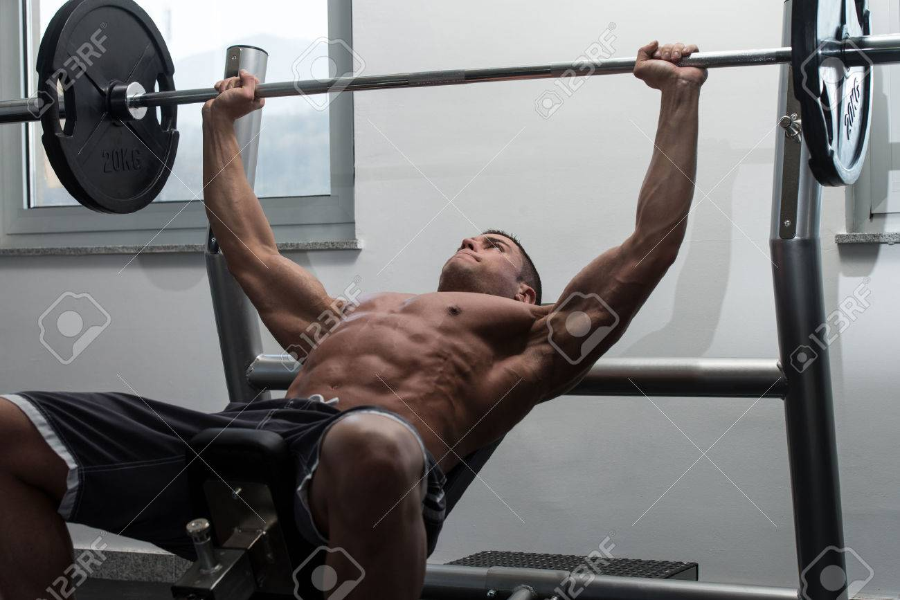 Young Man In Gym Exercising Chest On The Bench Press Stock Photo - 48647762