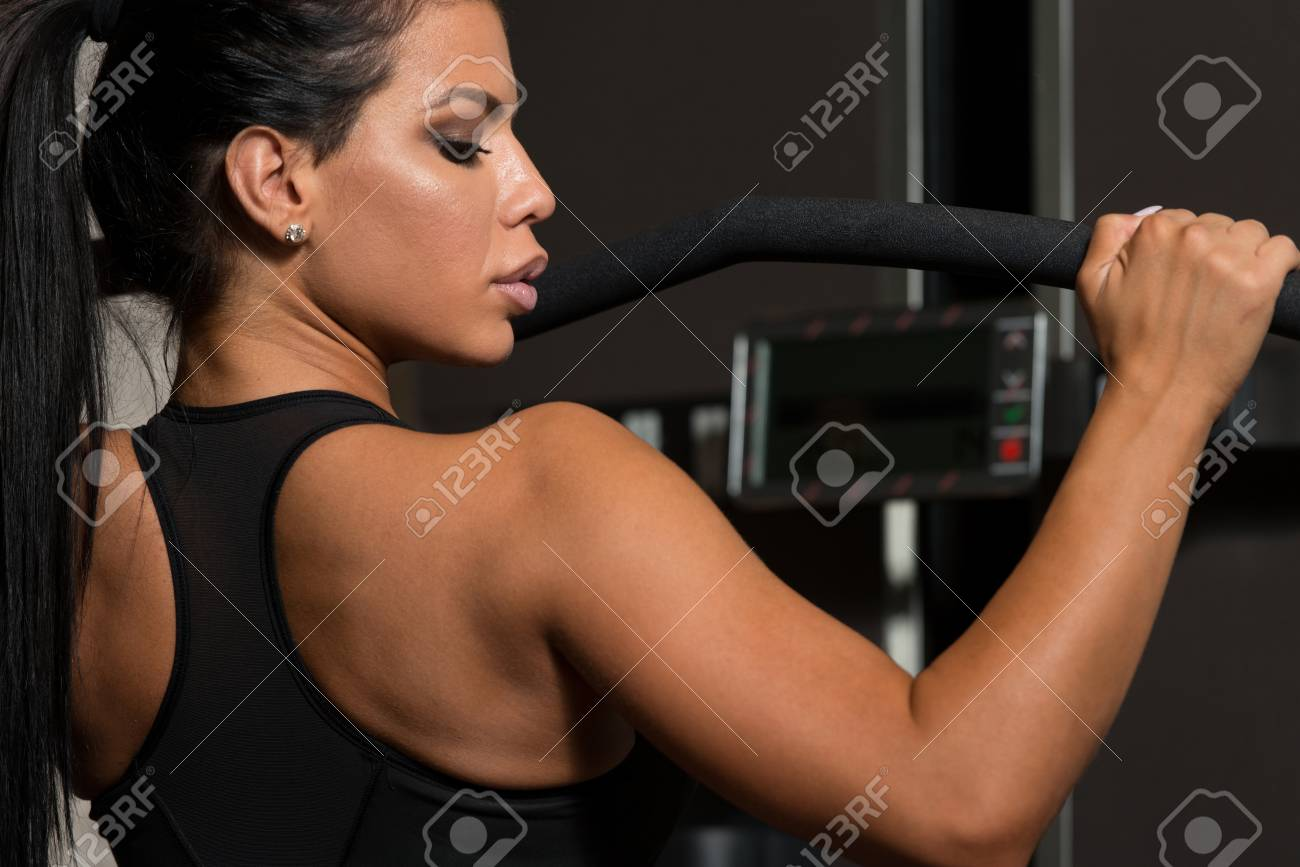Sexy Latino Woman Working Out Back On Machine In Fitness Center Stock Photo 50219427