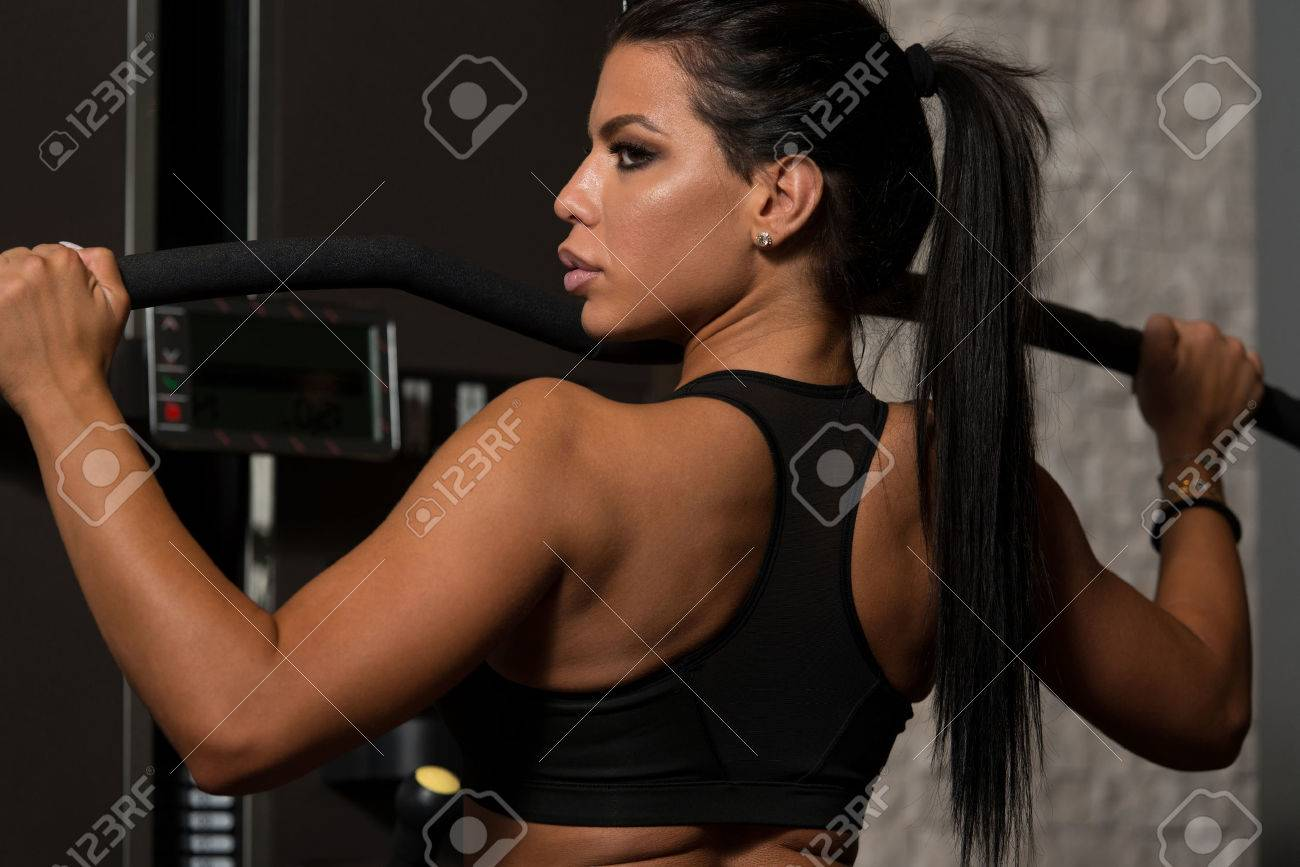 Sexy Latino Woman Working Out Back On Machine In Fitness Center Stock Photo 50219446