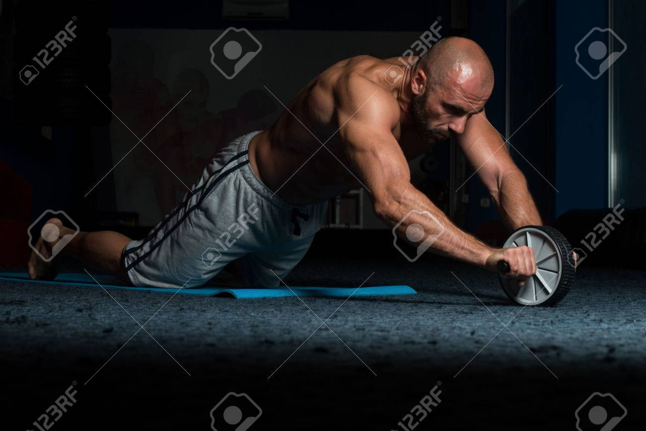 Young Man Exercising Fitness Workout For Abdominal With Toning Wheel Stock Photo - 57154215