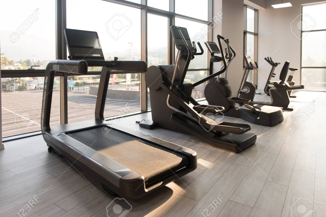 Modern gym room fitness center with equipment and machines stock