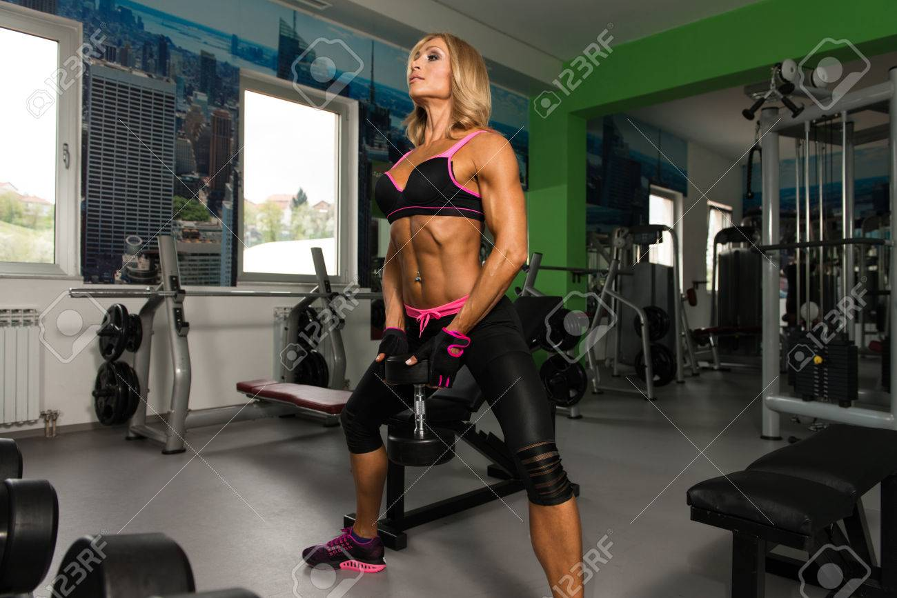 mature woman exercising butt with dumbbells in the gym and flexing