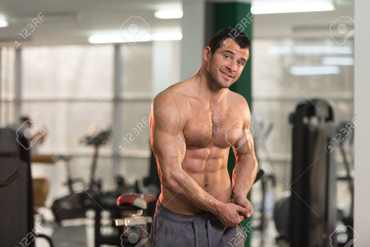 Hairy Handsome Young Man Standing Strong In The Gym And Flexing Muscles -  Muscular Athletic Bodybuilder