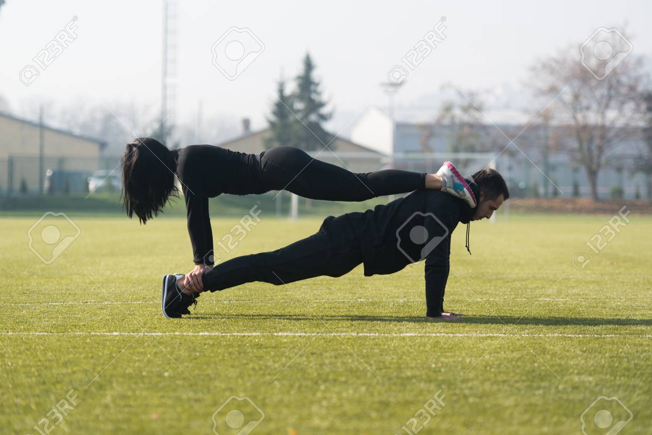 Attractive Couple Doing Push Up in City Park Area - Training