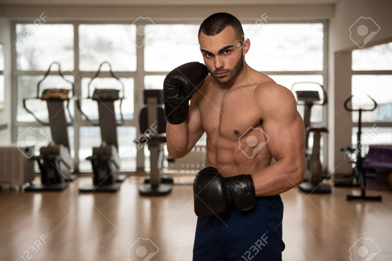 Stock Photo - Young Muscular Sports Guy In Gloves With A Naked Torso Boxing