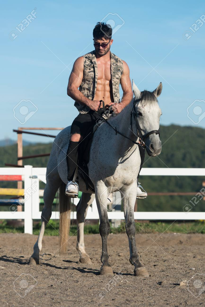 Handsome Macho Man Cowboy Riding On A Horse Background Of Sky