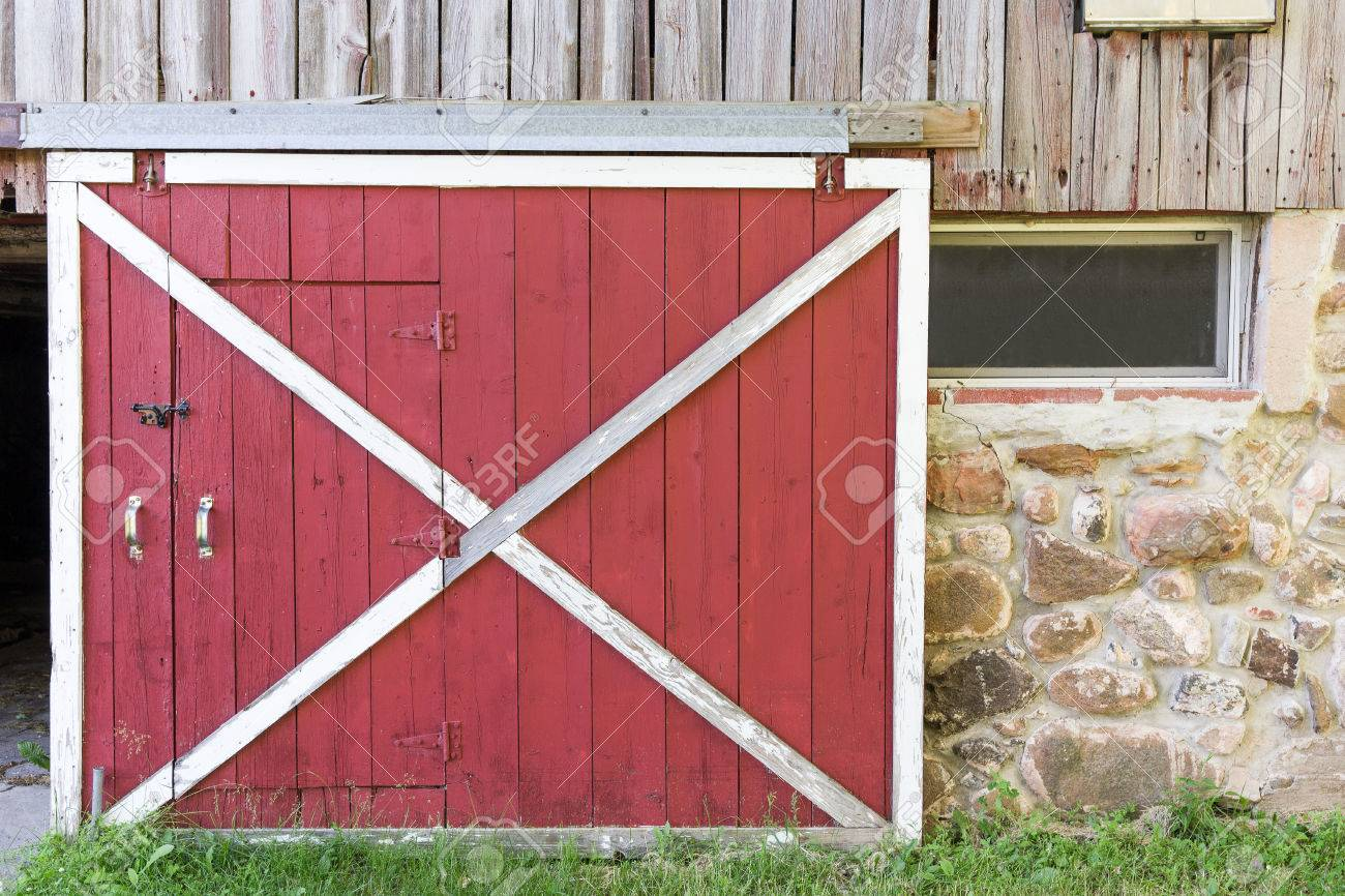 Partially Open Red Barn Door In A Weathered Barn Traditional