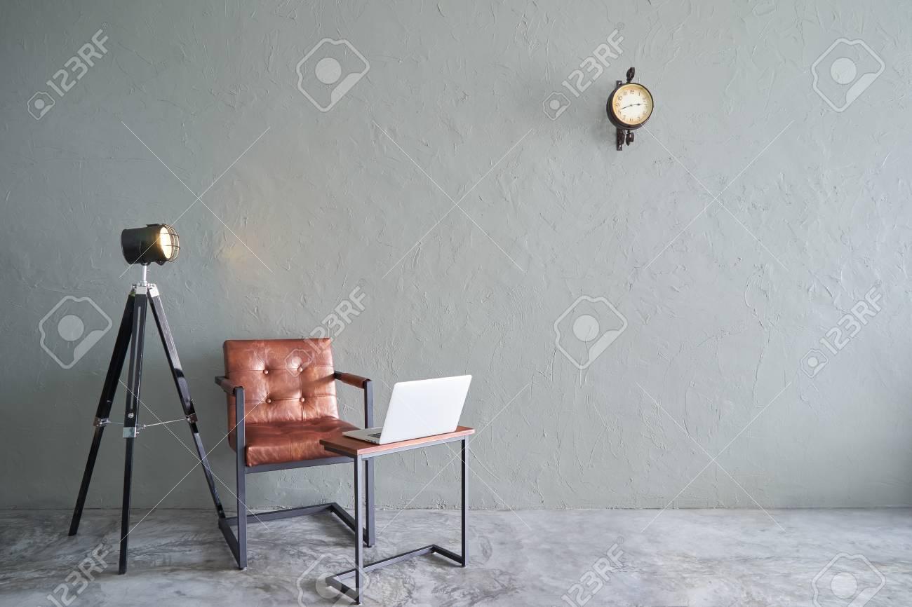 Soggiorno moderno con sedia in ferro marrone, orologio, tavolo da tè,  laptop e lampada stand. pavimento in cemento e muro di cemento, interior  design ...