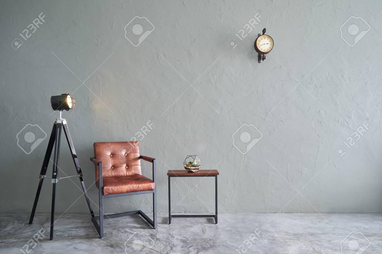 Soggiorno moderno con sedia in ferro marrone, orologio, tavolo da tè,  cactus e lampada stand. pavimento in cemento e muro di cemento, interior  design ...