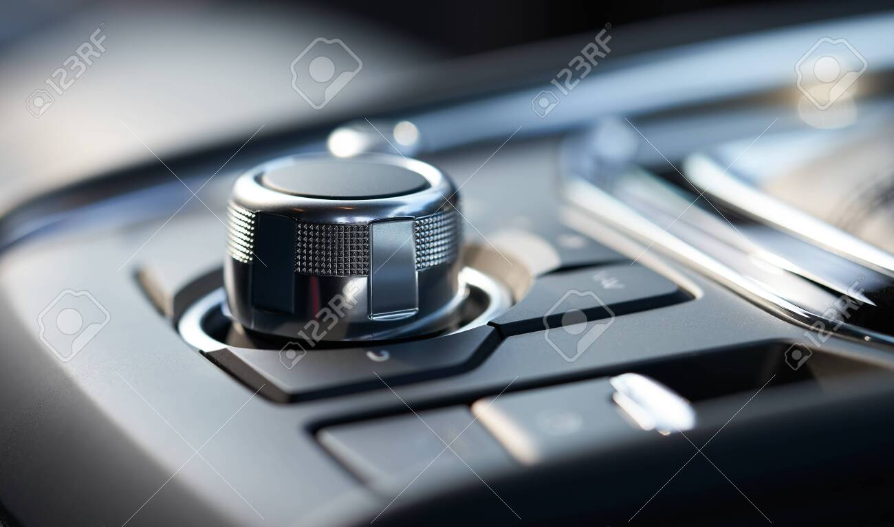 Closeup of a modern car interior with media and navigation control buttons - 129496412