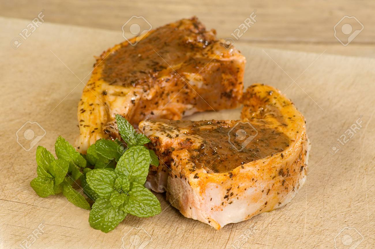 two uncooked minted lamb cutlets on a wooden board Stock Photo - 12750083