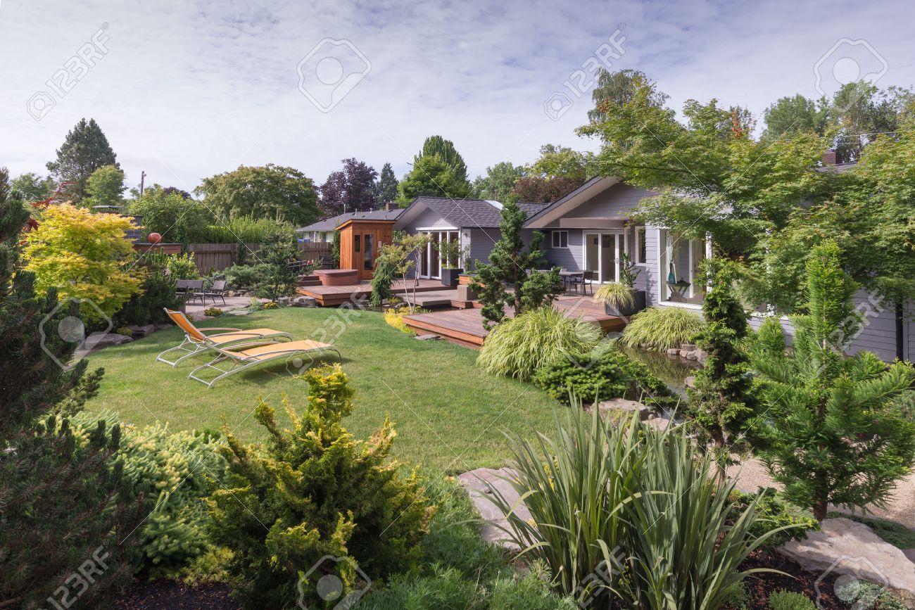 Une maison contemporaine peut être vu au-delà de la pelouse de jardin avec  de la roche et à feuilles persistantes aménagement paysager au premier plan  ...