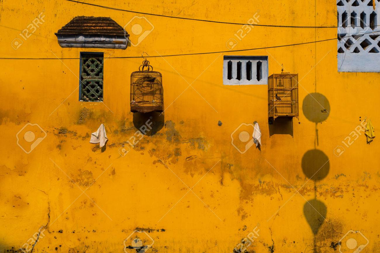 Yellow Wall With Small Windows And Bird Cages. Hoi An, Vietnam Stock ...