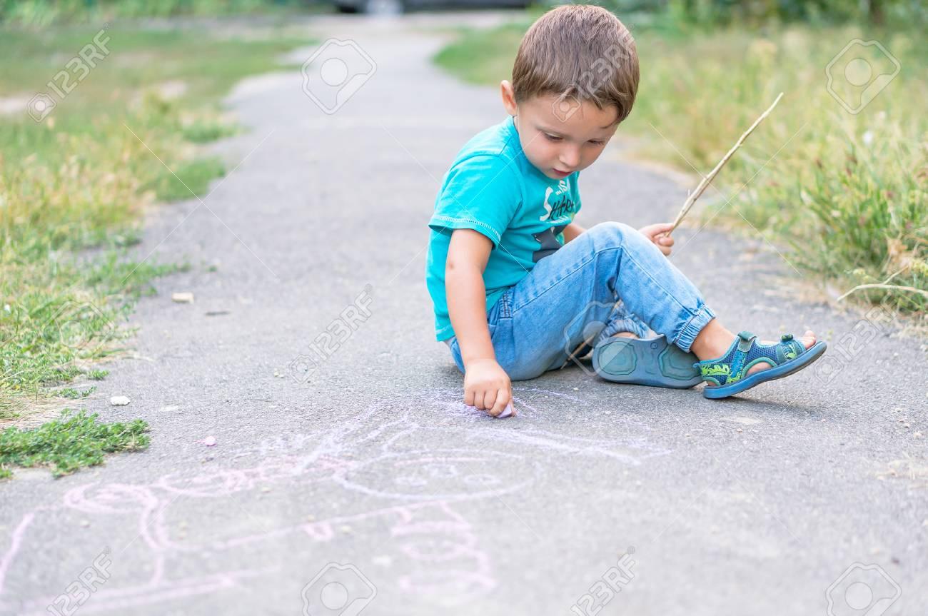 Disegno Di Bambino Che Corre : Ragazzo sveglio del bambino che disegna con il gesso sulla