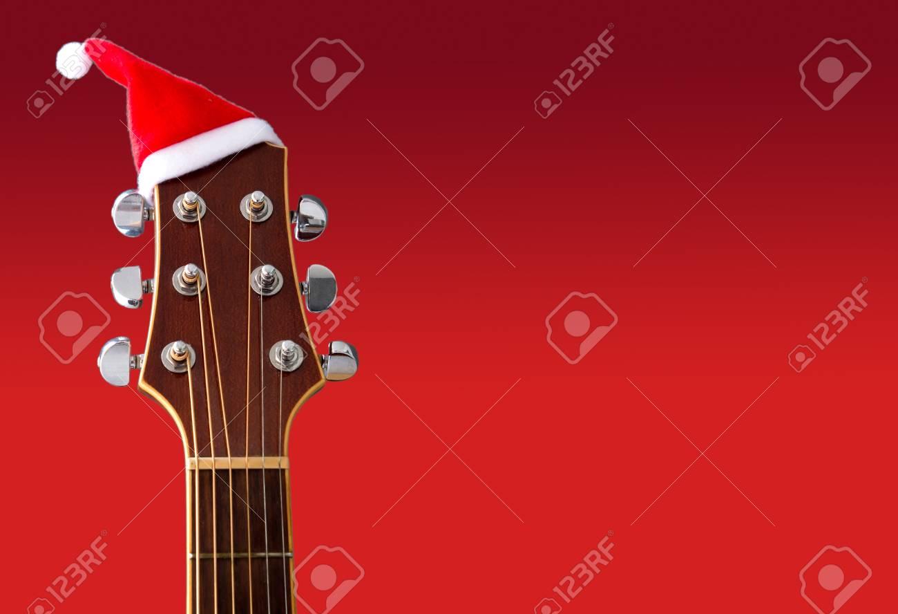 Chanson Un Joyeux Noel.Chapeau De Noel Rouge A La Guitare Avec Un Fond Rouge Chanson Joyeux Noel