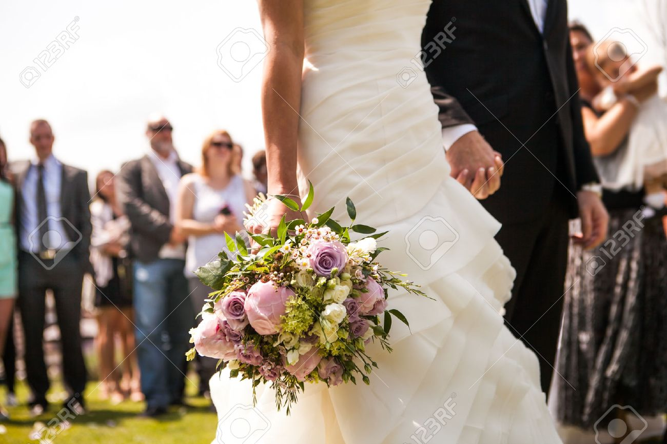 Moment in wedding,  bride and bridegroom holding hands with bouquet and wedding guests in background Stock Photo - 31487504