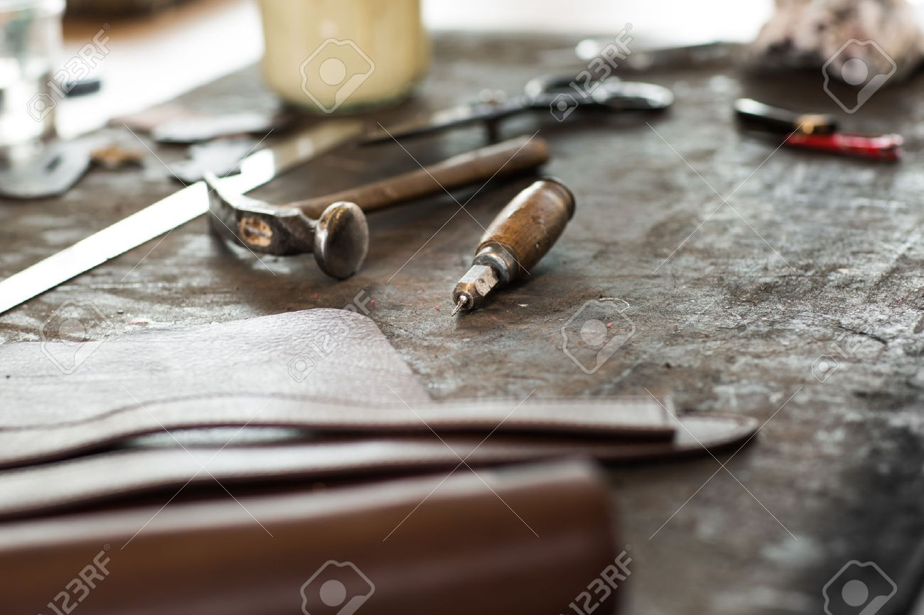 Leather crafting tools on working desk with a low depth of field - 31487511