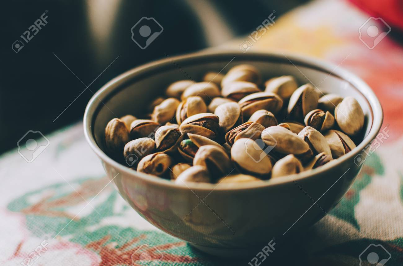 Pistachios in plate on home kitchen table - 90707280