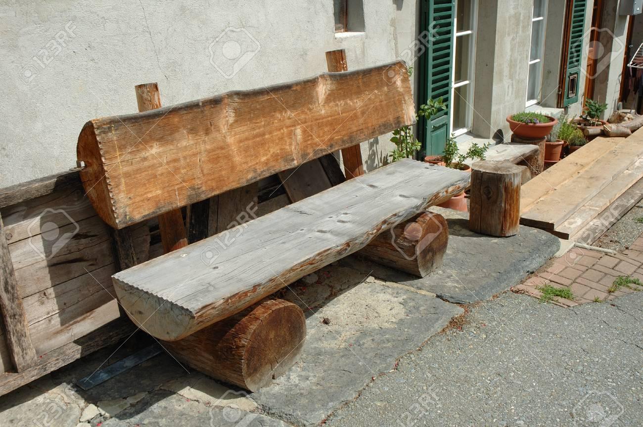 Vieux Banc De Bois Fait De Tronc Darbre Debout Au Mur Du Bâtiment