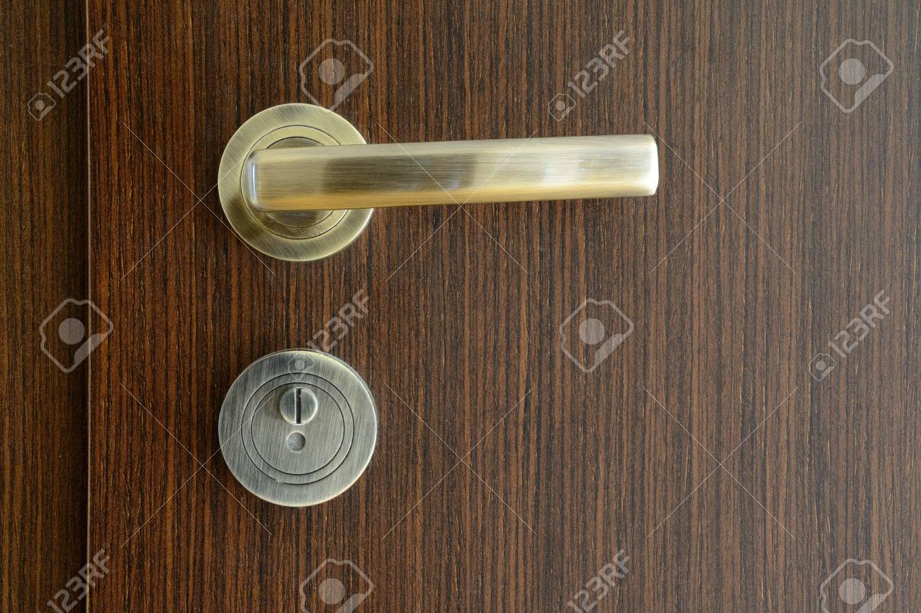 Golden modern door handle on brown wooden door stock photo 57838615