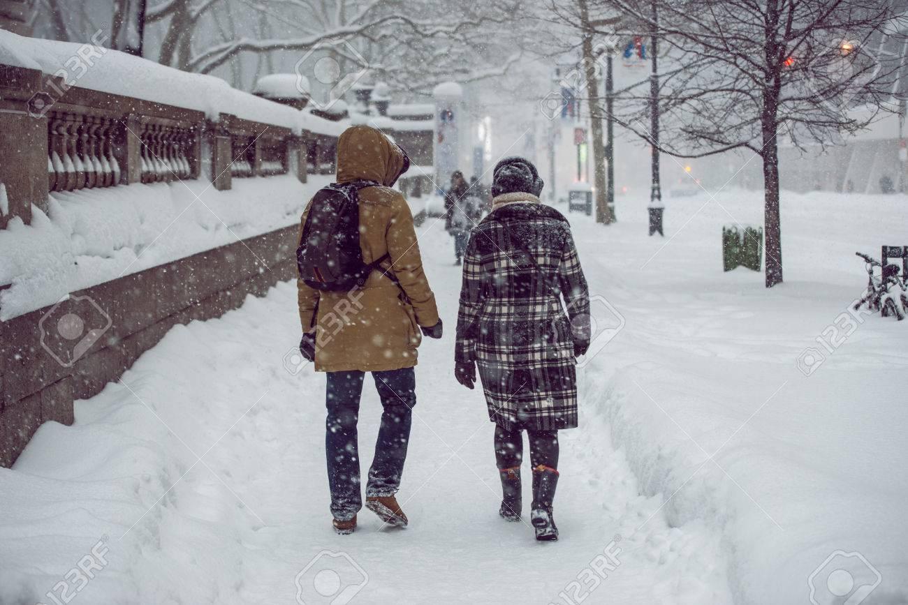 People walking on New York City Manhattan street during strong