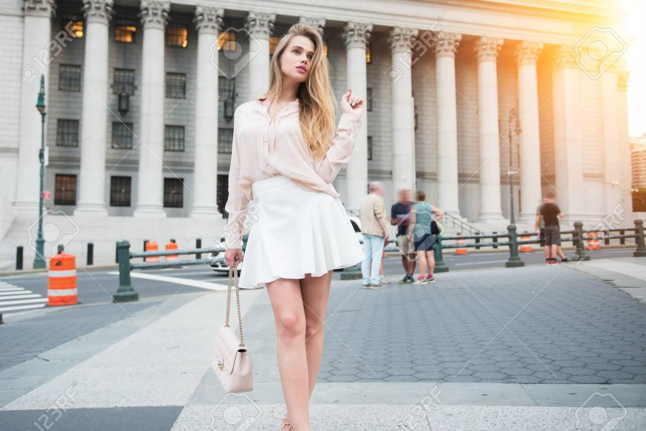 e9410dedcd59 Splendida giovane donna che cammina vicino edificio della città indossando  vestiti abbigliamento estivo.