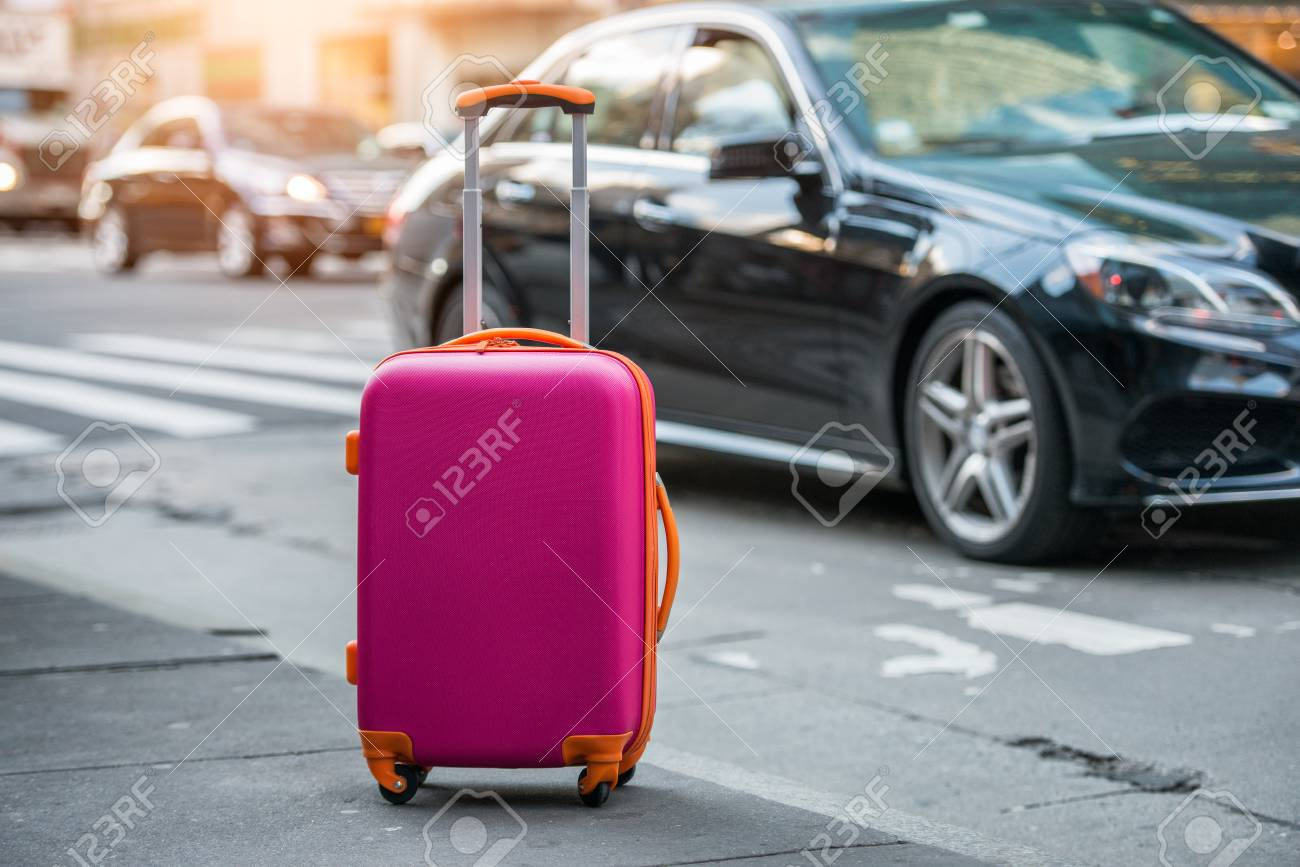 Luggage bag on the city street ready to pick by airport transfer taxy car. - 74002434