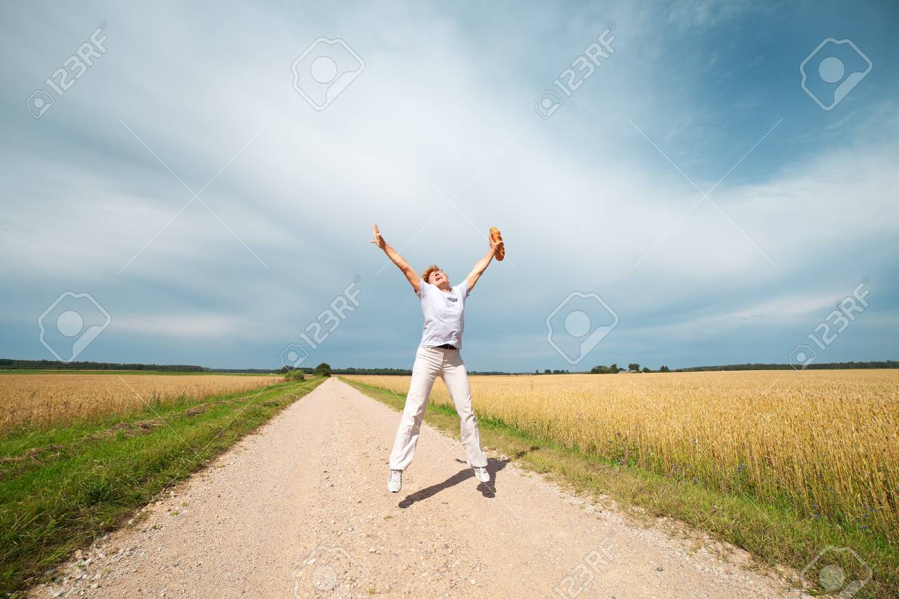 Woman and bread at ripe wheat field Stock Photo - 14604509