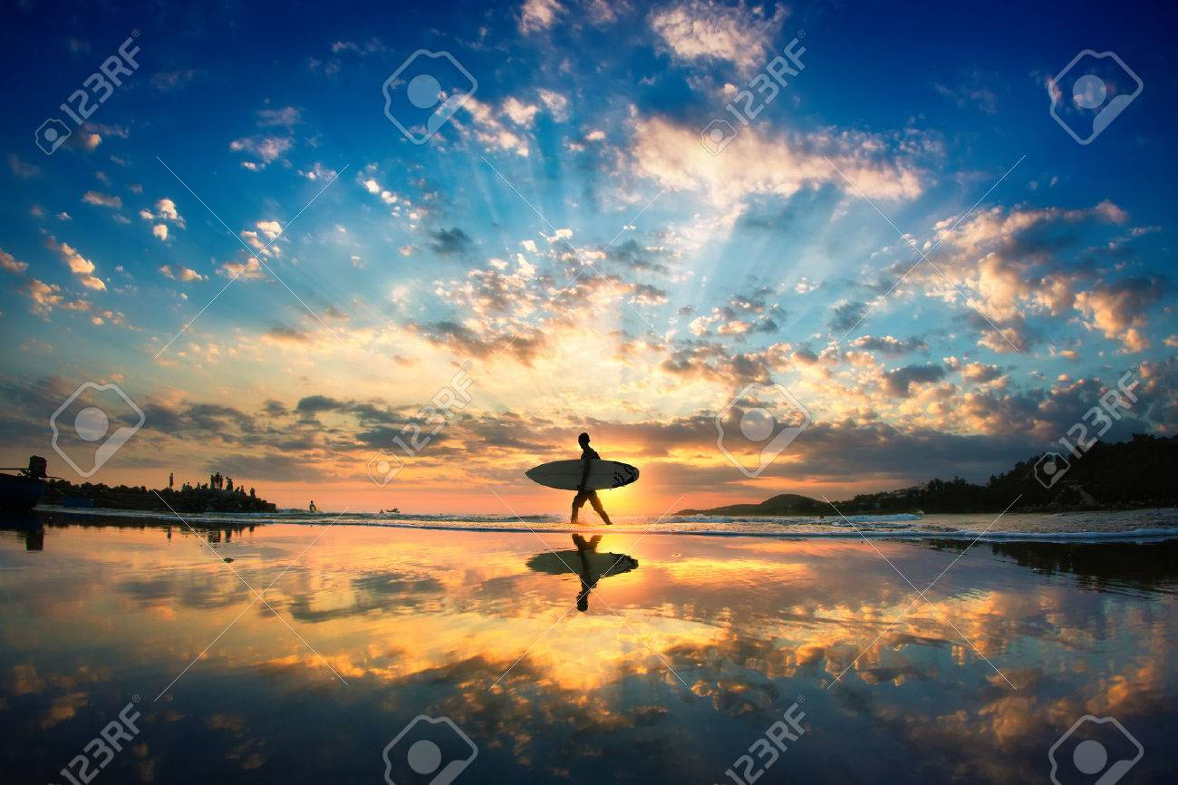 Sun surfer. A man is walking with a surf in his hands across the sea shore. - 44228894
