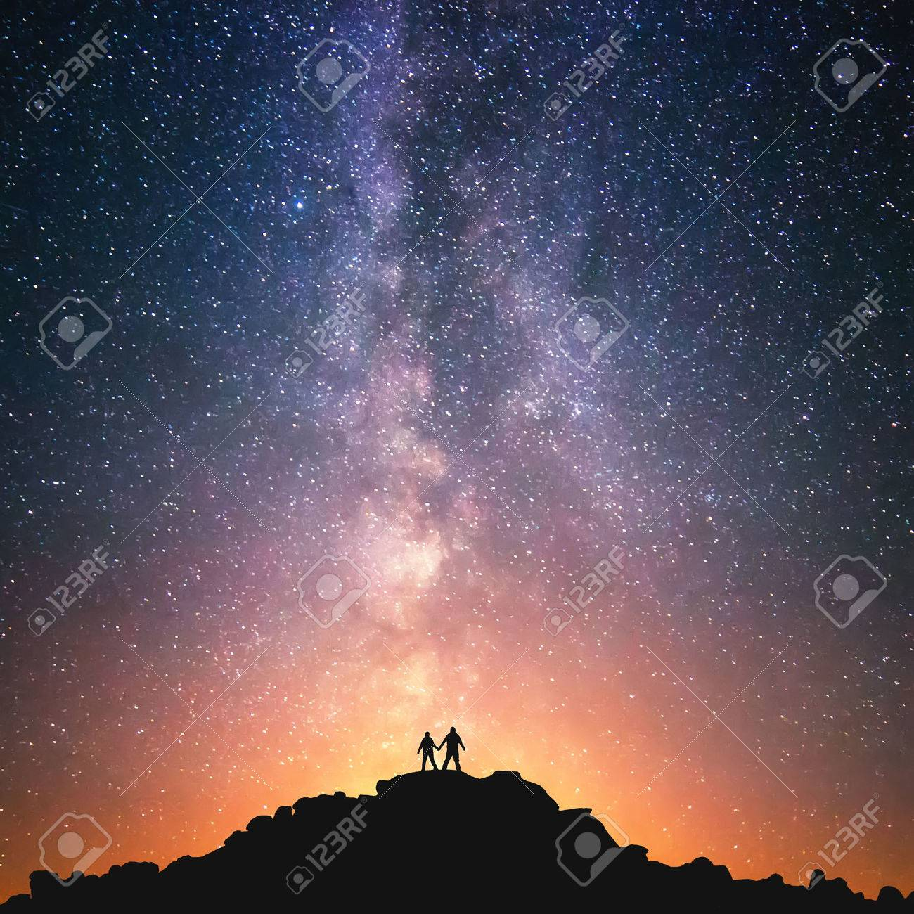 Silhouttes of two people standing together holding hands against the Milky Way on the top of the hill. - 48581910