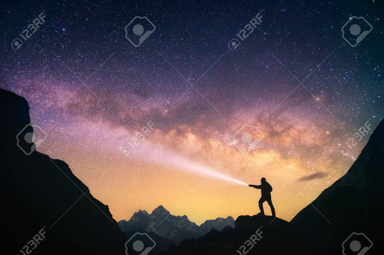 Silhouette of the man standing against the Milky Way in the mountains with a flashlight in his hands. Nepal, Everest region, view of the mount Thamserku 6,608 m from Thame village 3,750 m. - 52058606