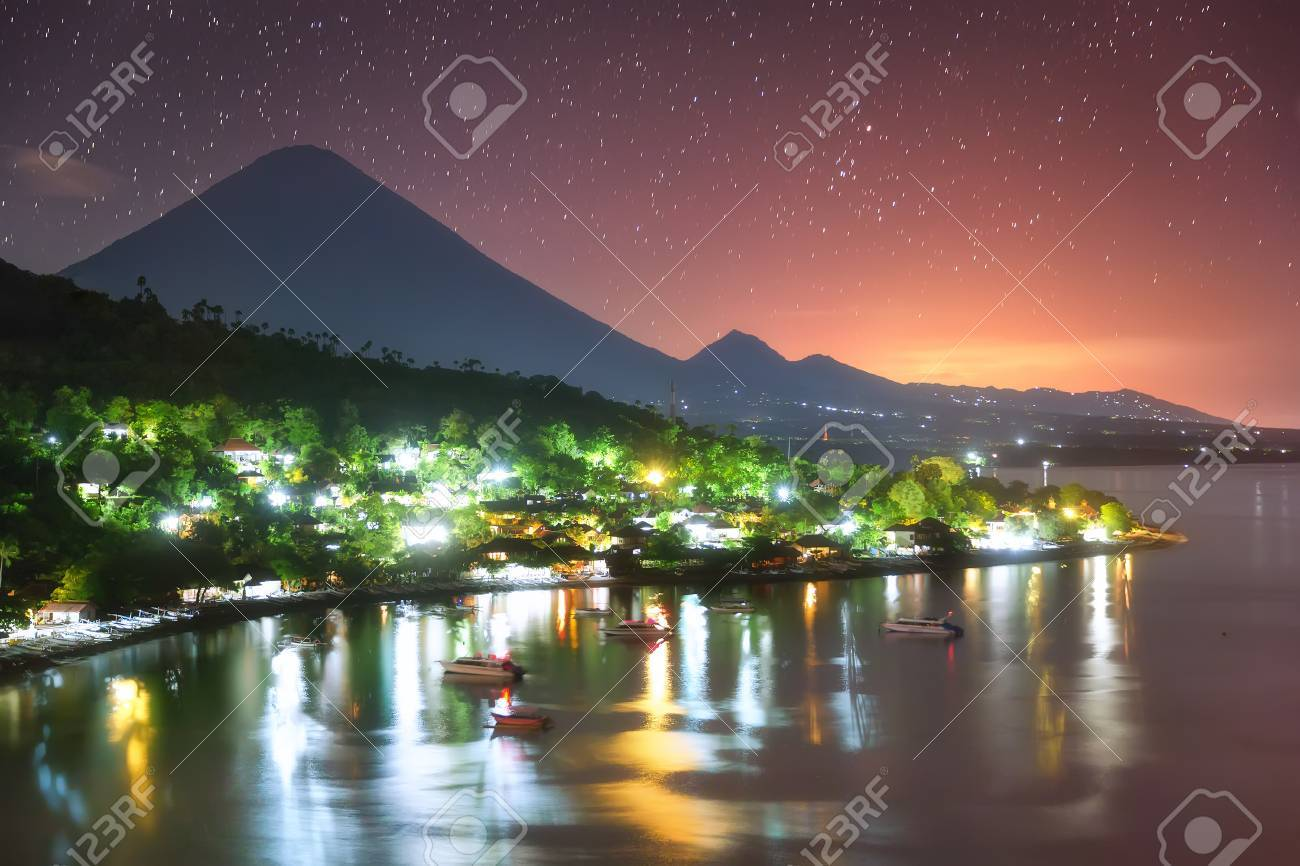 Colorful Amed harbor in the night and the highest point of the island, Agung volcano (3,142 m) is visible on the background. - 64930481