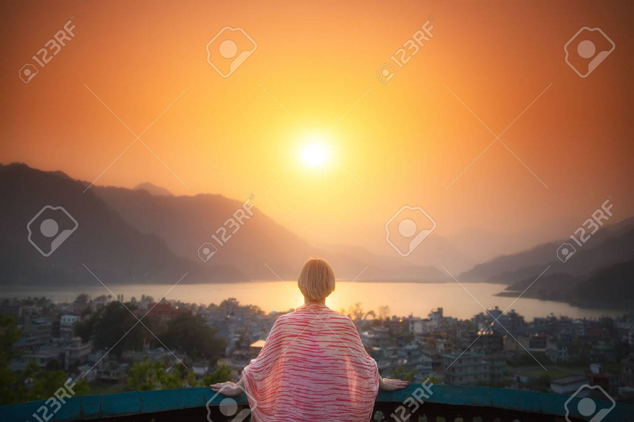 Bright future. Mature woman is standing on the terrace looking at the beautiful sunset over the lake and mountains. - 64114988