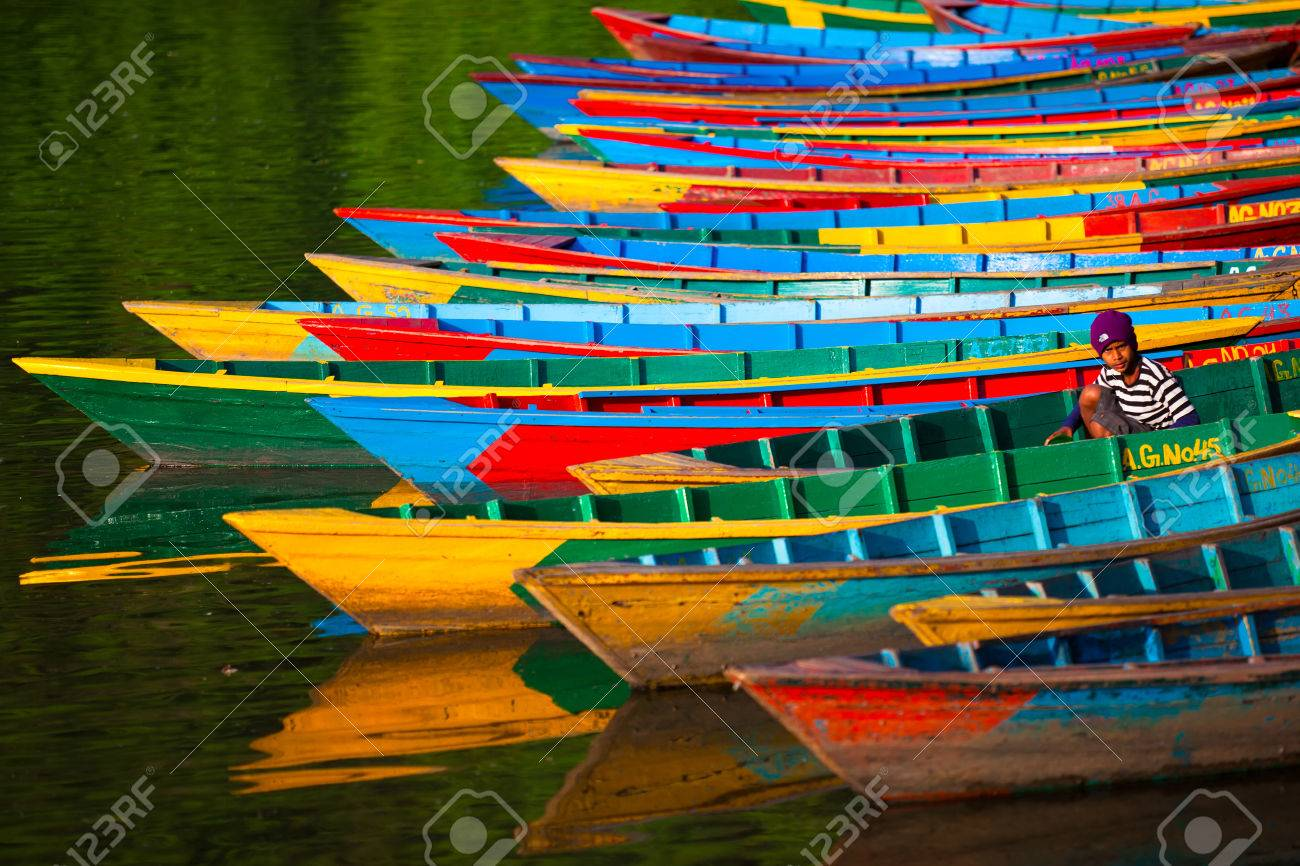 Colorful moorage. Bright and colorful boats standing in one raw on the water. A boatman (young nepali boy) is sitting in one of them. - 82710720
