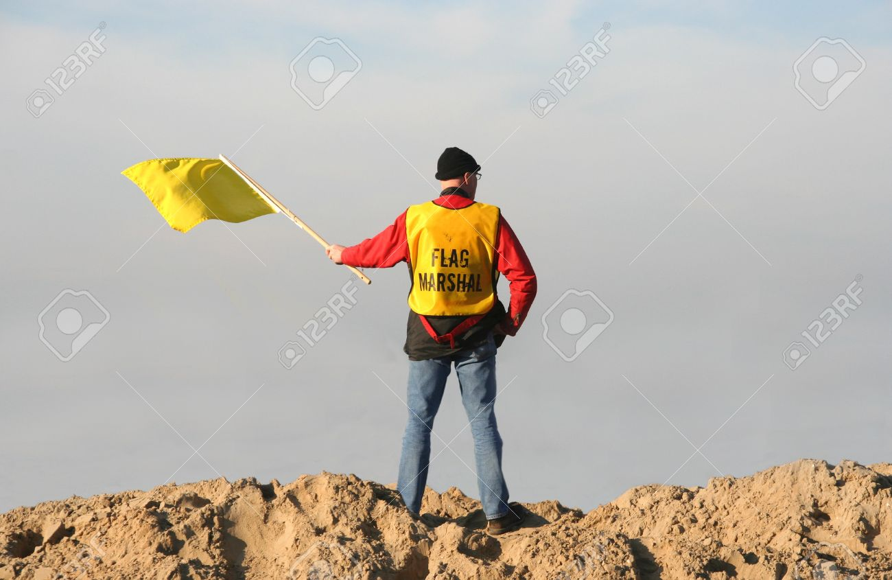 Flag marshal waving the yellow flag at Red Bull motorcross race in Scheveningen, Holland on November 18, 2007 Stock Photo - 8150711
