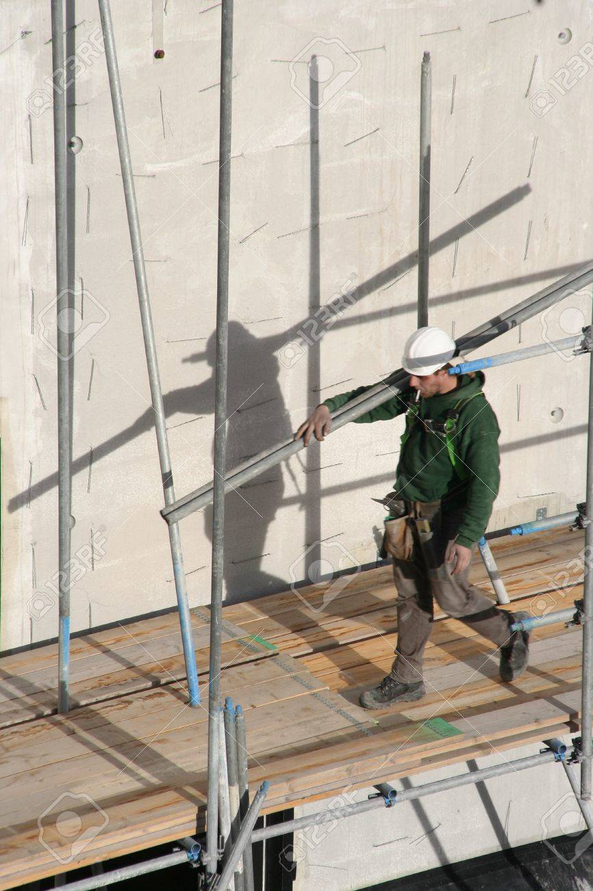 Construction worker carrying scaffolding, smoking a cigarette in The Hague, Holland. Picture taken on February 16. 2007 Stock Photo - 8150716