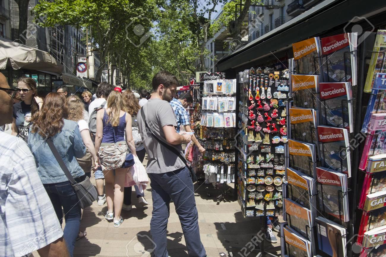 Barcelona, Spain - May 28, 2015: Tourists walk and buy postcards