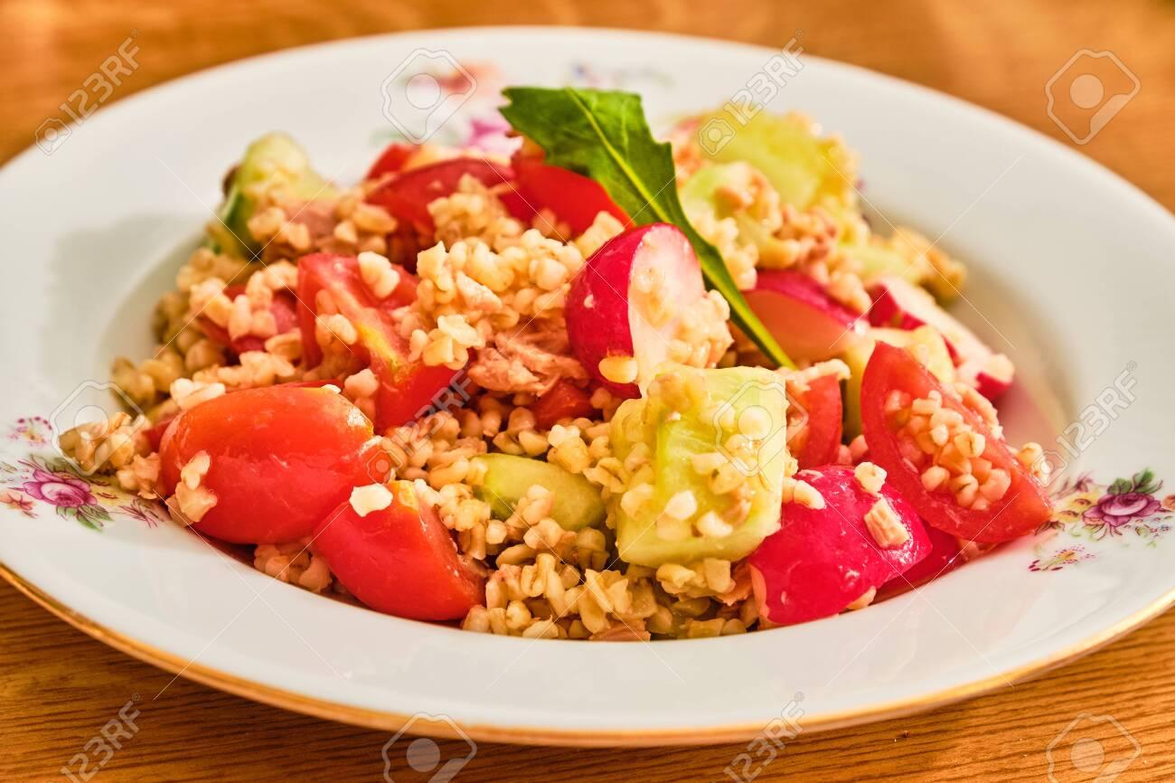 Tasty bulgur salad with tuna, radish, tomato and cucumber on white plate on wooden table - 152806199