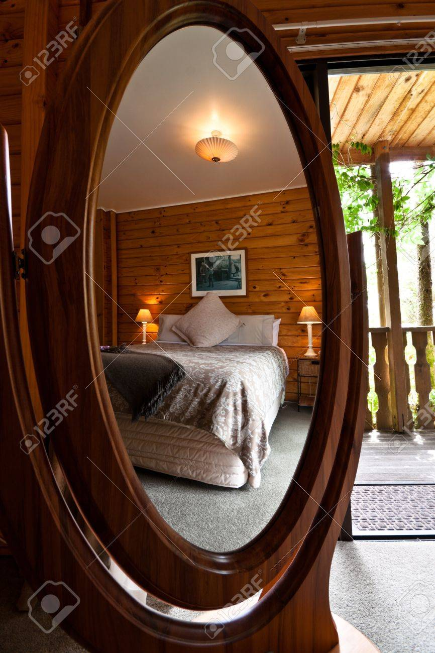 Nice Warm Bedroom Interior Of Mountain Lodge Reflected In Mirror