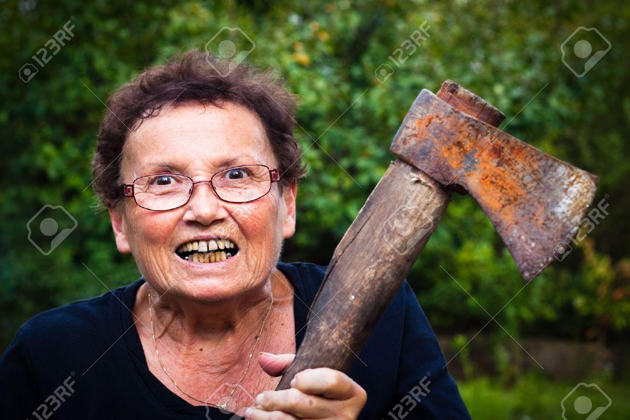 Crazy senior woman holding axe. - 11048678