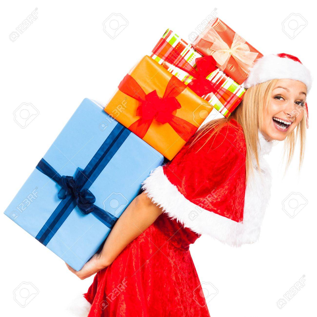 Young beautiful blond laughing woman holding stack of colorful gift boxes wearing Christmas Santa costume, isolated on white background. Stock Photo - 16008536