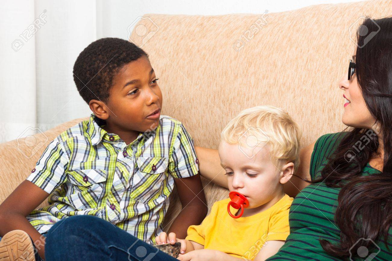 Detail of young woman speaking with children on sofa. Stock Photo - 16969275