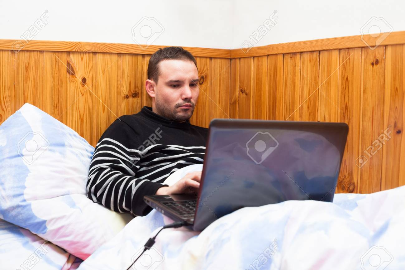 Young man lying in bed and using laptop. Stock Photo - 17752092