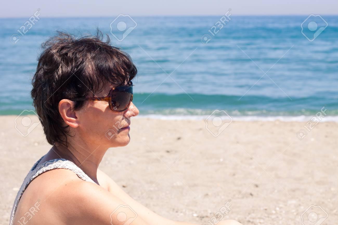 43a7a5d1c96a Archivio Fotografico - Ritratto di donna di mezza età di relax sulla  spiaggia.