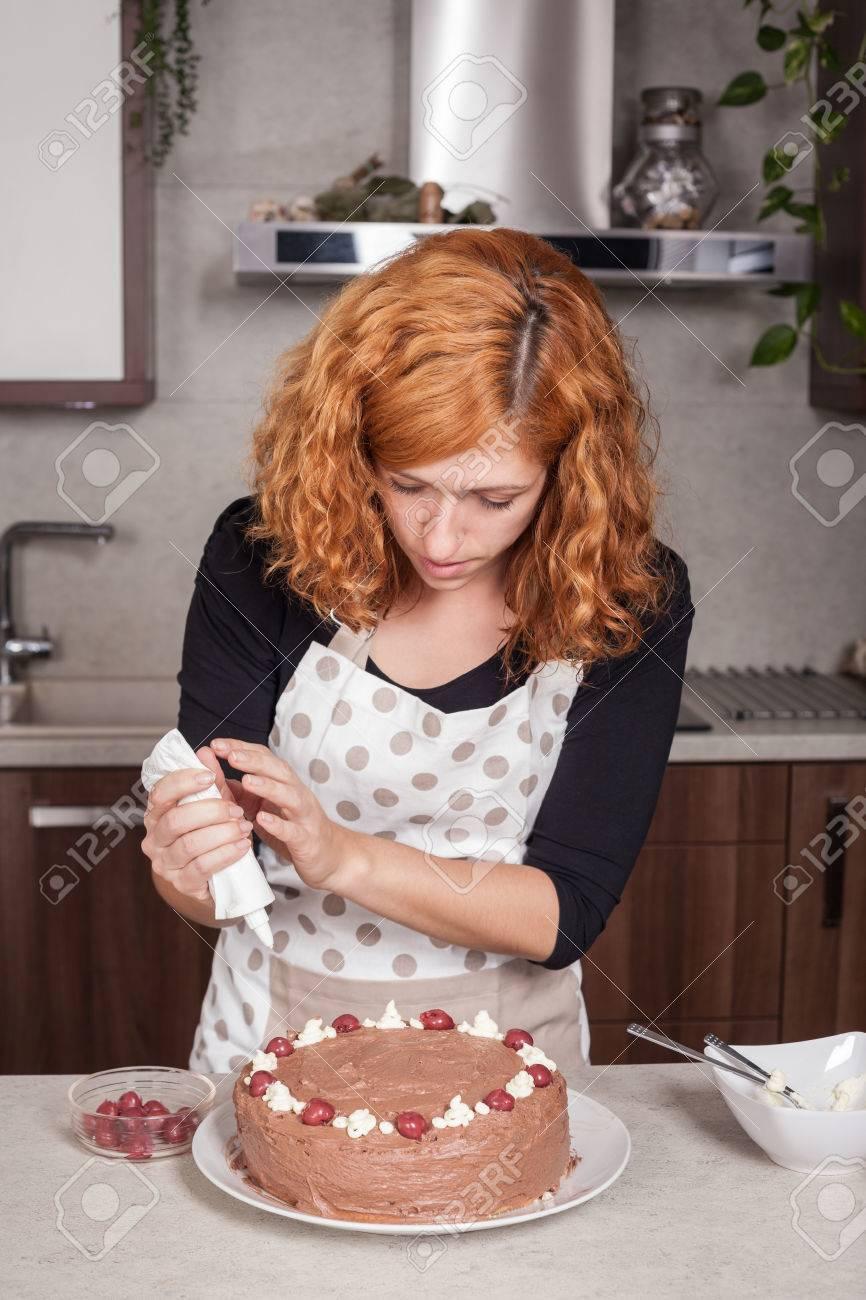 redhead woman decorating homemade chocolate cake in the kitchen redhead woman decorating homemade chocolate cake in the kitchen at home stock photo 38687343