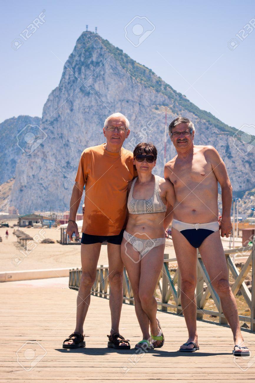 f55ab84e4f29 Archivio Fotografico - Ritratto di due uomini anziani e donna di mezza età  in posa per la foto sulla spiaggia con Gibilterra roccia sul fondo.