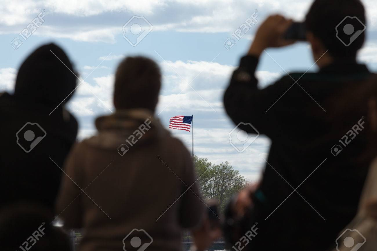 Silhouettes of travelers looking at the flag of the United States of America. - 44029851