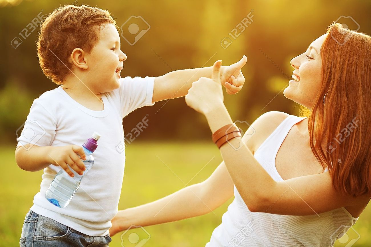happy family having fun. baby boy with brown curly hair and  his mother with ginger hair showing thumb up each other. outdoor shot Stock Photo - 16121992