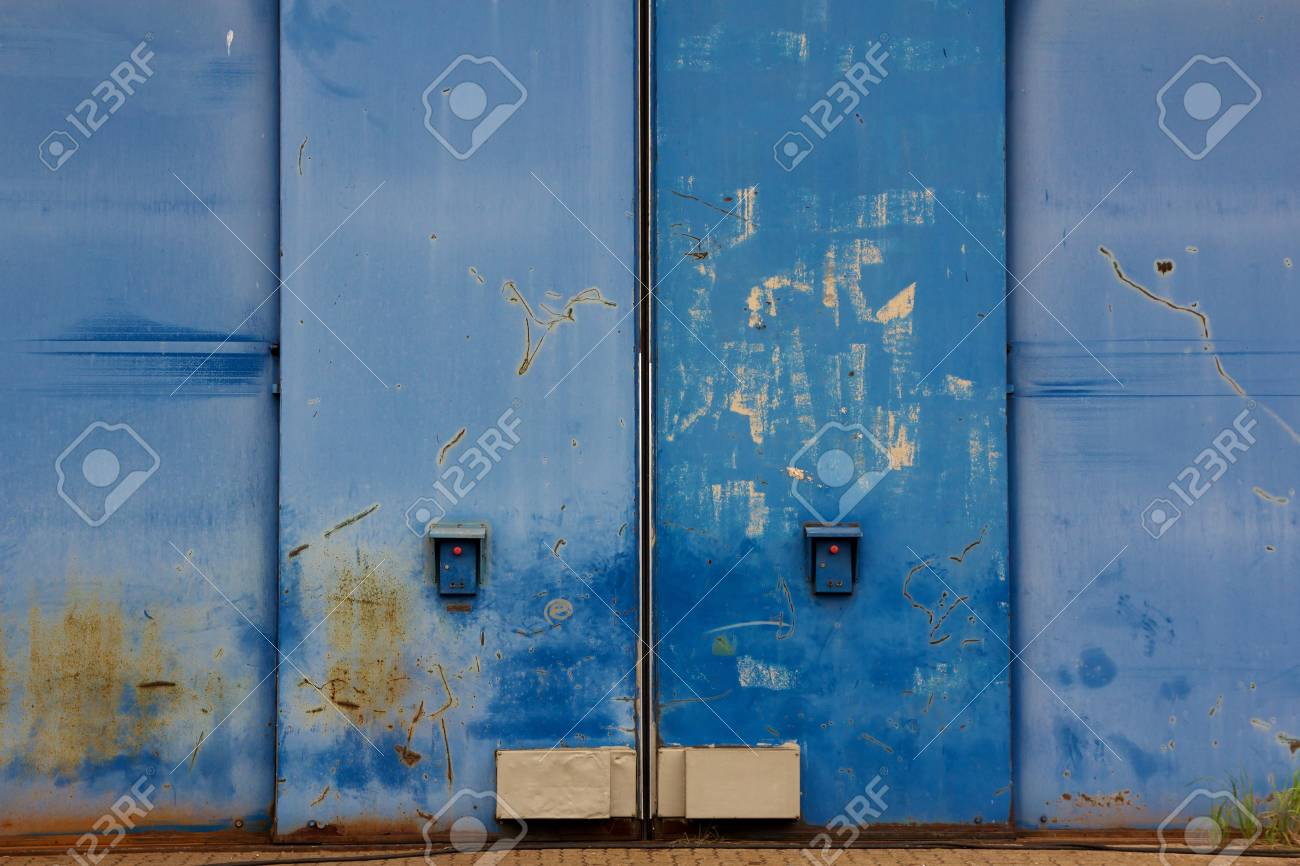 Weathered blue hangar gate with control elements resembling a Human face Stock Photo - 14274004